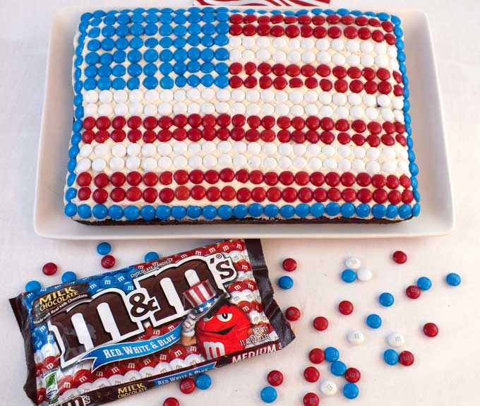 This M&M Flag Cake could not be easier to decorate and it is a great last minute Fourth of July dessert for a 4th of July party. You can decorate this fun Red White and Blue 4th of July Cake in less than 30 minutes. Pin this great 4th of July treat for later and follow us for more fun and patriotic 4th of July Food Ideas. #4thofJuly #fourthofjuly #4thofJulyTreats #4thofJulyDesserts #4thofJulyFood