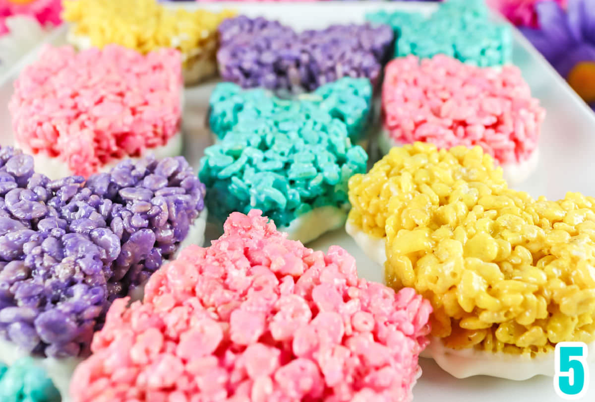 Close up on the bottoms of colored Rice Krispie Treats that have been dipped in White Chocolate.