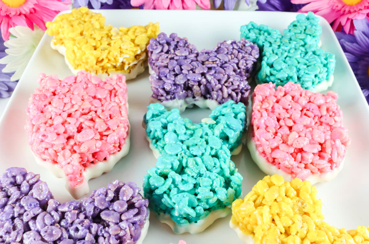 Closeup of a white platter filled with colorful Rice Krispie Treats that have been dipped in White Chocolate.