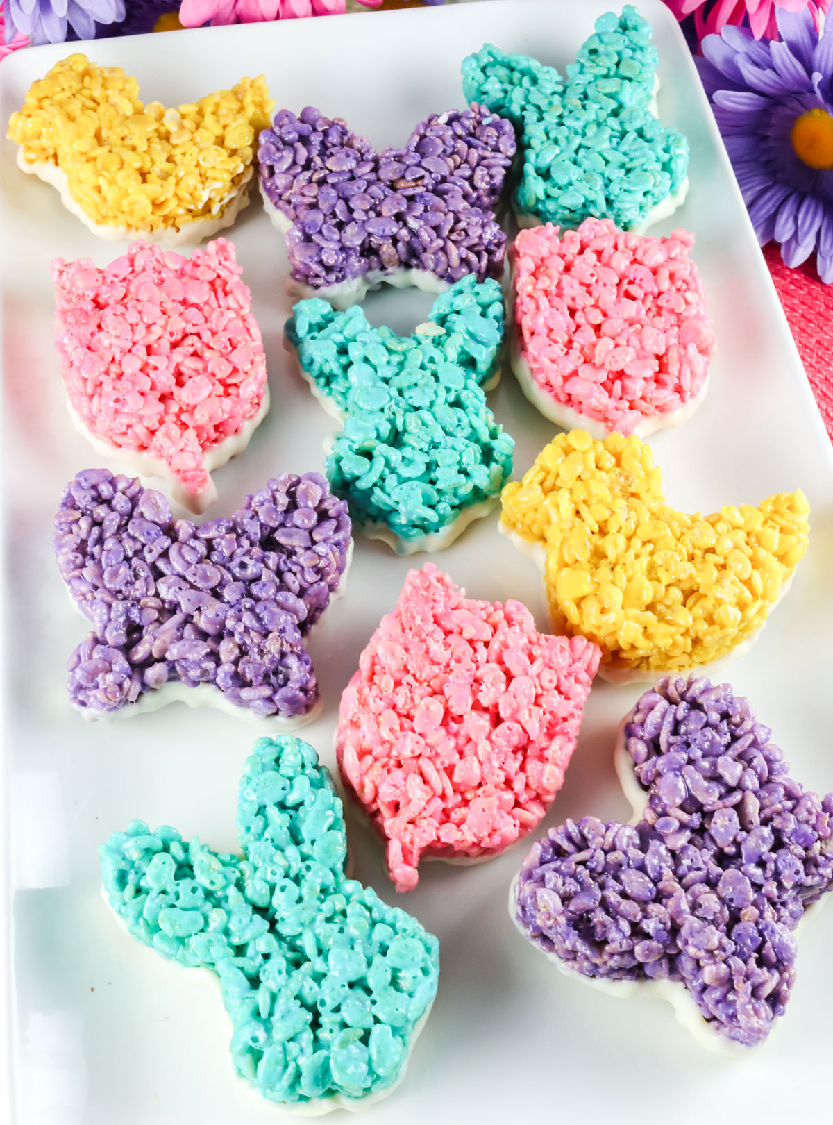 A large white platter covered with Blue, Purple, Pink and Yellow Rice Krispie Treats dipped in White Chocolate surrounded by pink and purple decorative daisies.