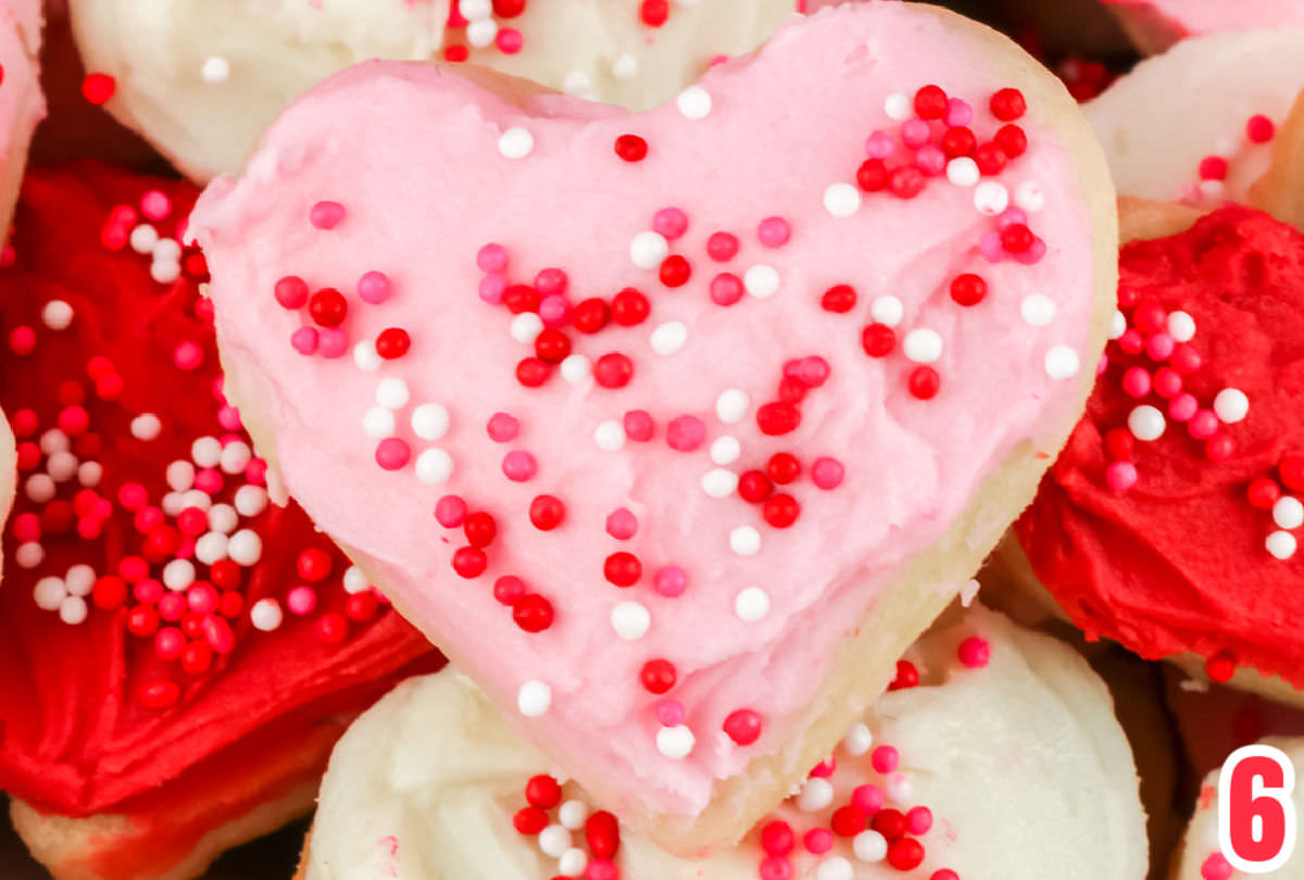 A closeup of a heart-shaped Sugar Cookie frosted in pink frosting and covered in red, pink and white sprinkles.