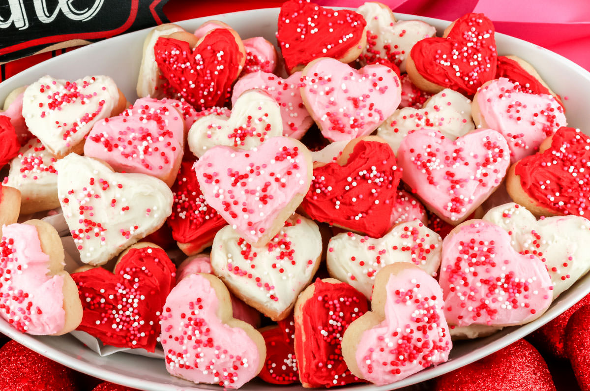 A white serving bowl filled with Mini Heart-shaped Sugar Cookies frosted in Pink, White and Red Buttercream Frosting and topped with Valentine's sprinkles.