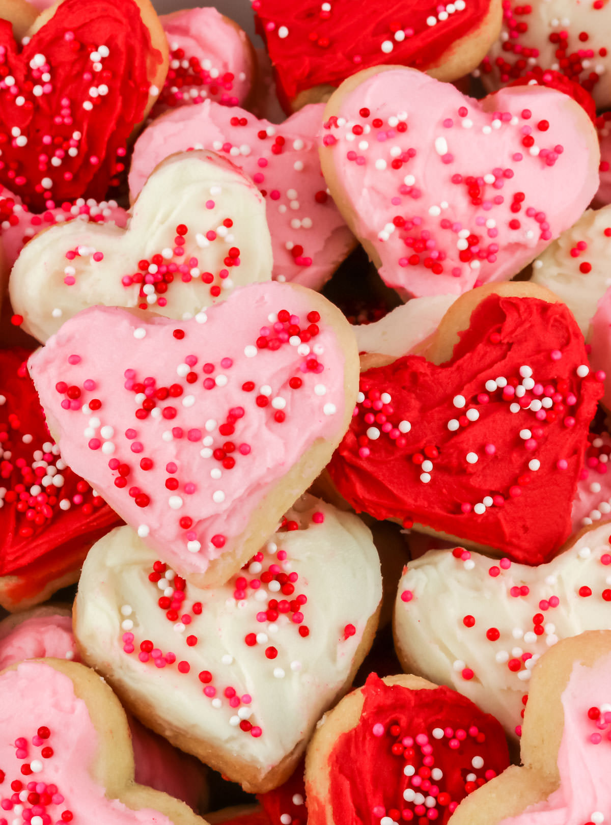 A closeup on a stack of red, white and pink heart-shaped Valentine's Frosted Sugar Cookies.