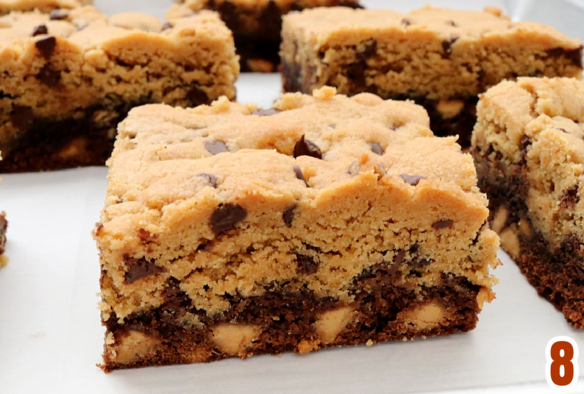 Closeup on individual bars of Peanut Butter Brookies sitting in rows on a piece of parchment paper.