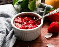 strawberry compote in small white pot with spoon