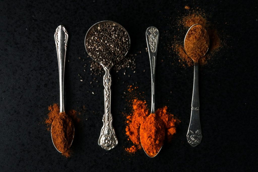 Spoons with spices on a black stone plate