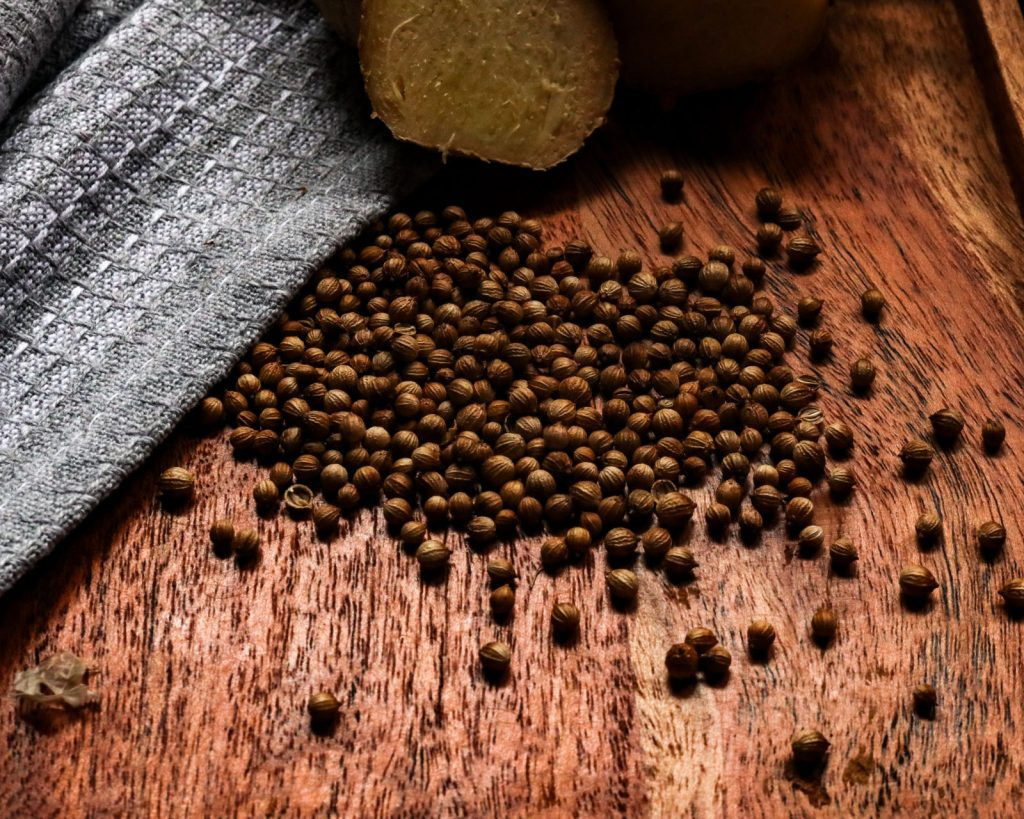 coriander seeds and Ginger root on a wooden underground