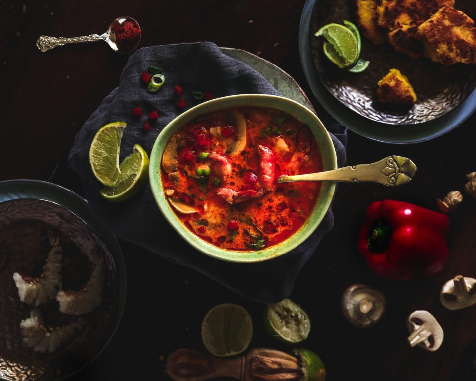 red soup in a light green bowl with vegetables and spice around