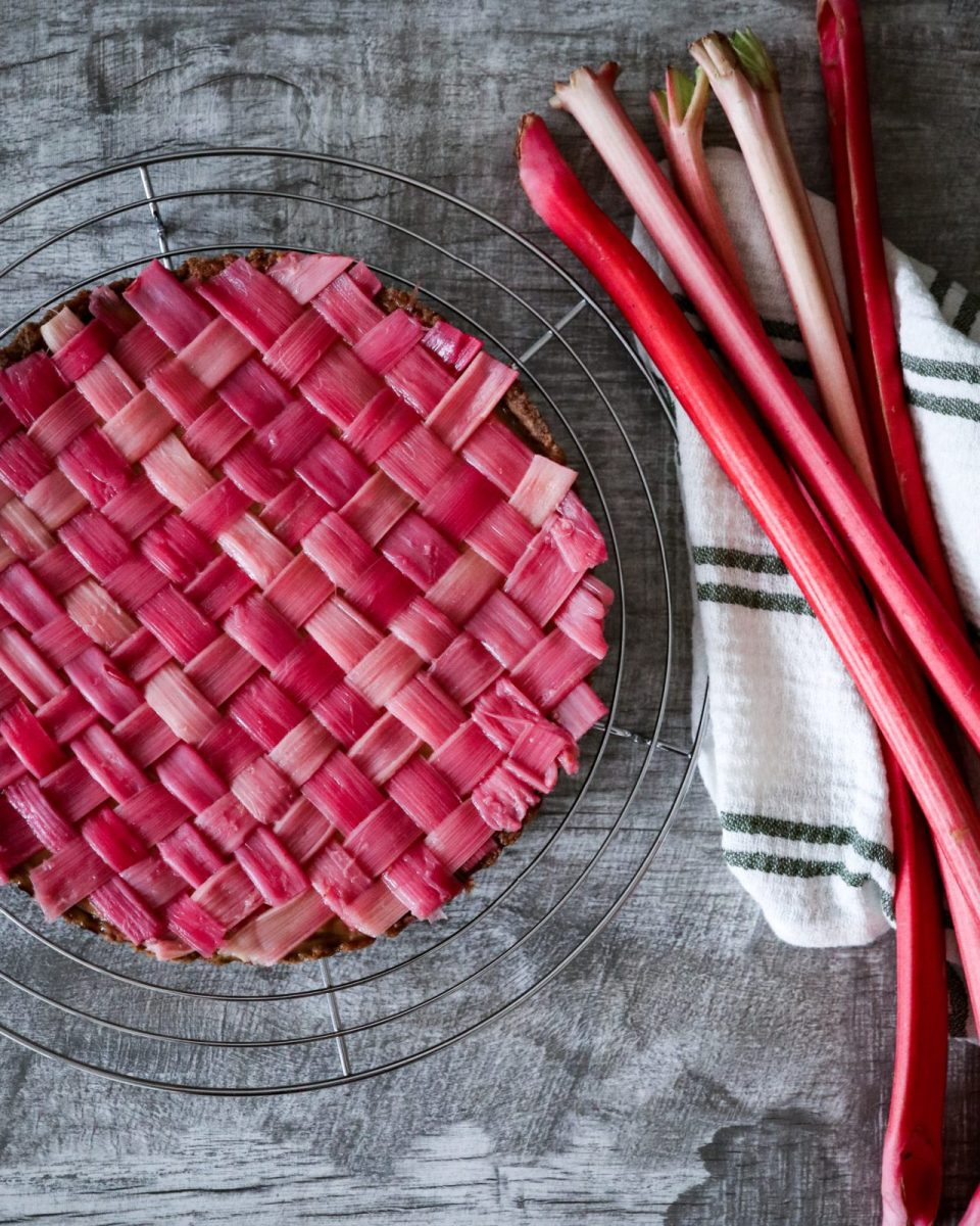 Rhubarb lattice Taste placed on a cooling rack, white green striped kitchen towel and rhubarb.