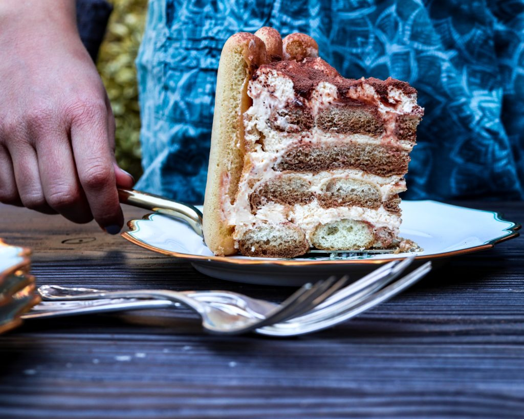 a Slice of an tiramisu cake on a white plate with someone in the background
