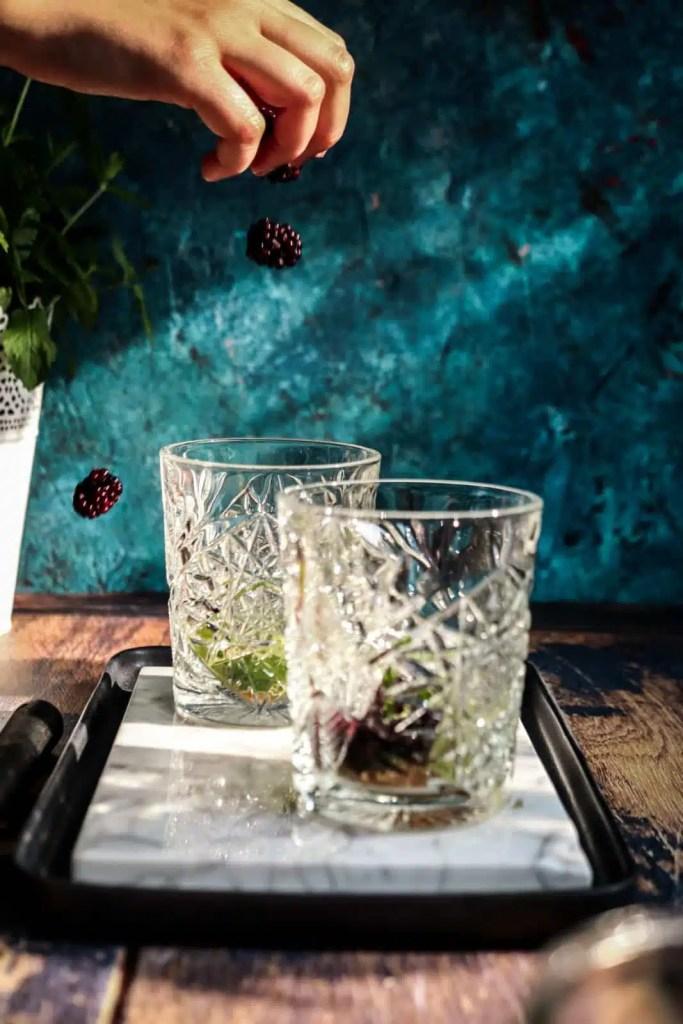 Falling blackberries into glasses