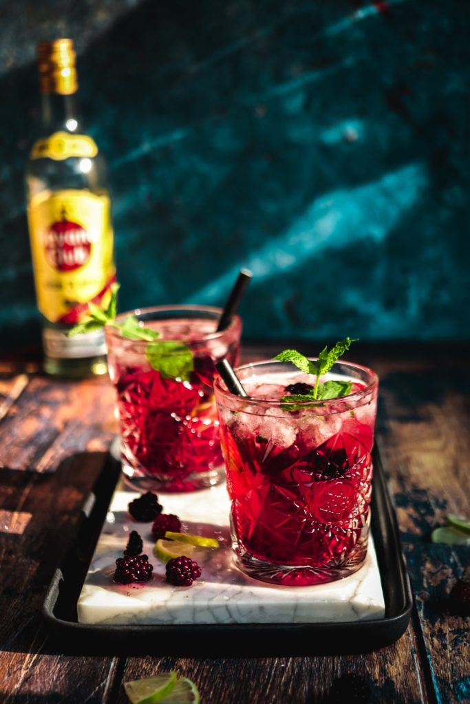 summer nights blackberry-lavender mojitos on a white marbled square with a bottle in the background