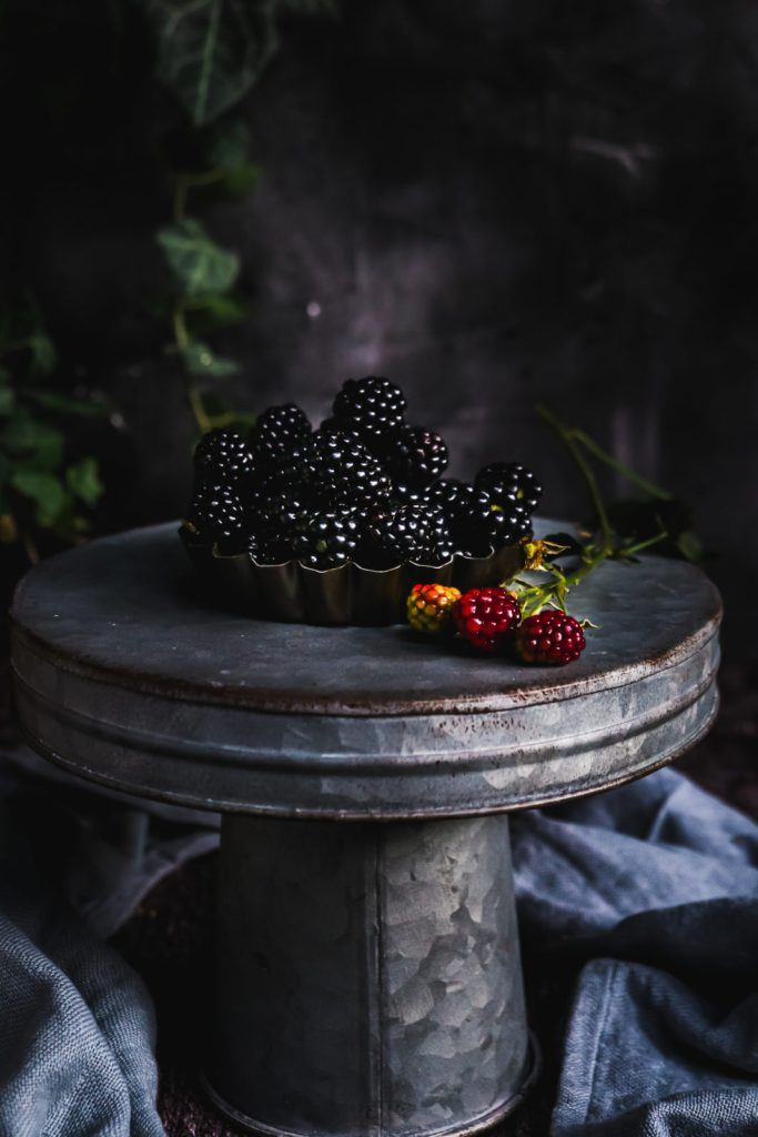Fresh blackberries in a small tart form on a metallic cake stander