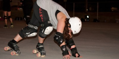 Roller Derby skater takes her position as she begins to start a new bout at league practice.