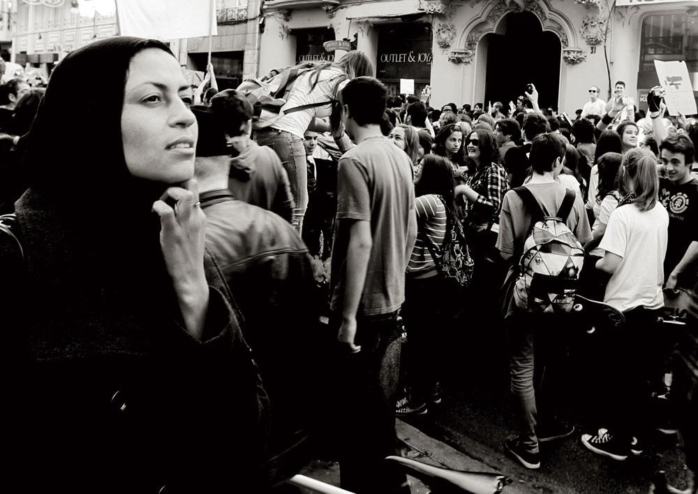 Una mujer de origen marroquí observa una protesta de estudiantes. Febrero de 2012.