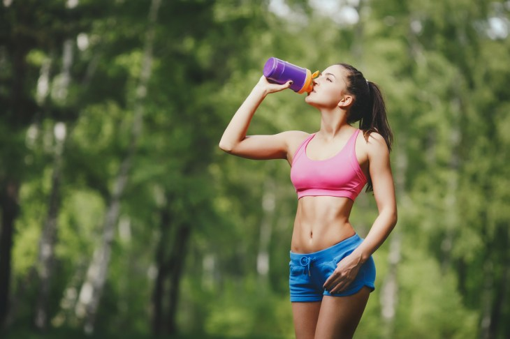 Fitness woman drinking water after running at park