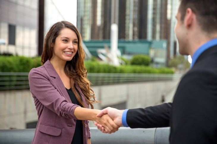 Handshake two business executives downtown buildings man and woman perfect smile teeth hair skin