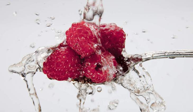Raspberries being washed on spoon | Fruits and Veggies That Can Keep You Hydrated