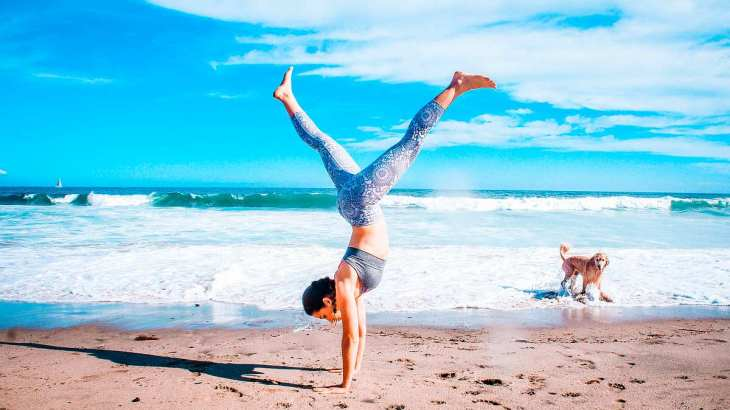 Woman performing inverted stand beside seashore | Benefits Of Drinking Water