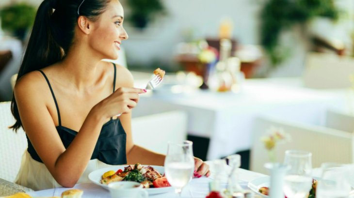 Beautiful woman eating meal restaurant | Ways To Drink More Water This Year