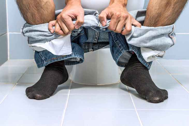 Man sitting on toilet | Alkaline Water as a Natural Remedy for Constipation