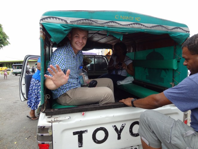 Tyler Cramer riding in the back of a covered pickup truck through Fiji