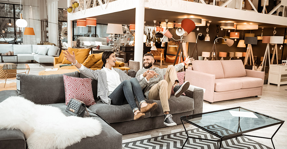 Cheerful laughing couple behaving childishly in furniture showroom making furniture shoppers happy