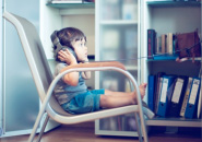 A young child sitting on a chair listening through headphones