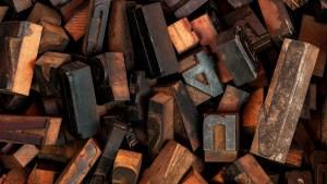 a jumble of wooden letterpress blocks Type Club