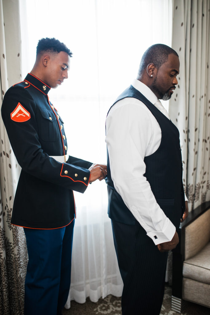 a groomsman in military blues helps a groom get ready before his wedding at The Westin San Jose