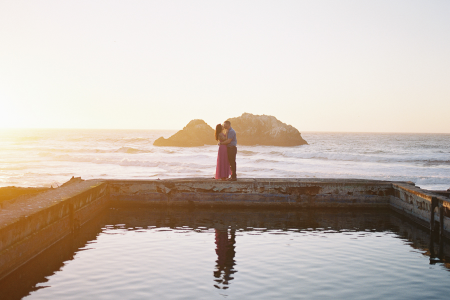 a couple cuddling in front of the sunset during engagement photos at Sutro Baths