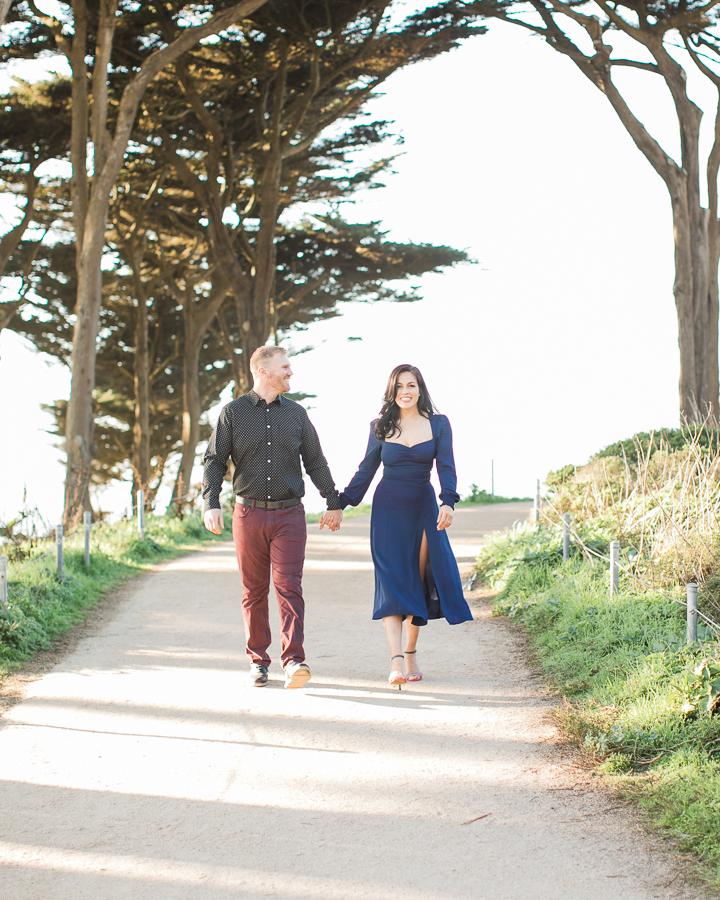 a couple walks through the park during engagement photos at Sutro Baths
