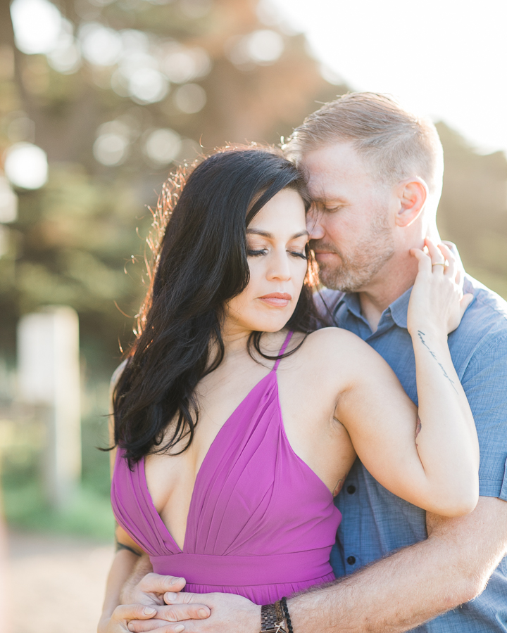 a romantic cuddle between a couple during engagement photos at Sutro Baths