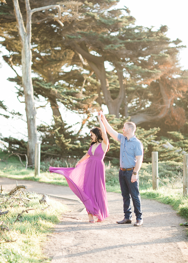 a groom twirls his bride during engagement photos at Sutro Baths