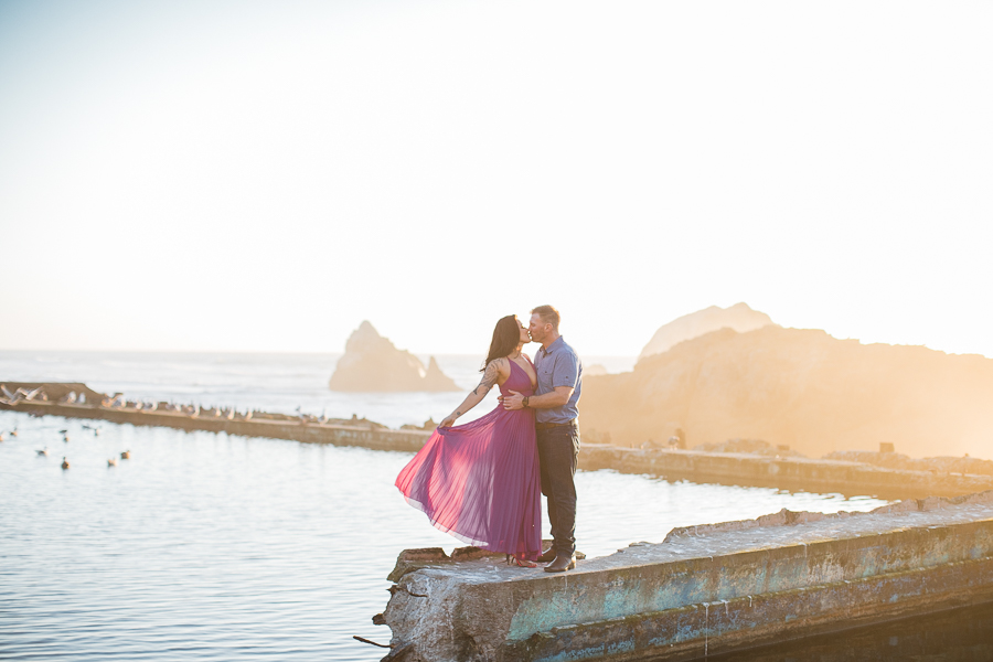 a couple kisses during engagement photos at Sutro Baths