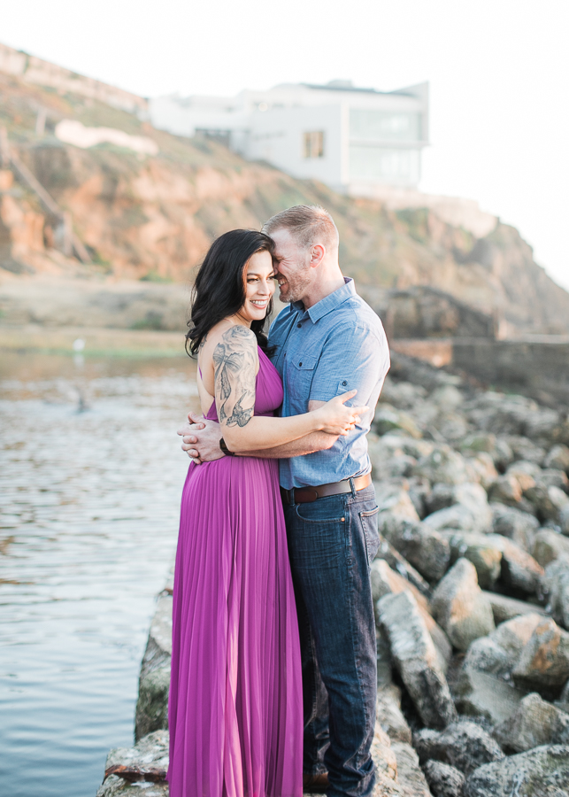 a couple lauging during engagement photos at Sutro Baths