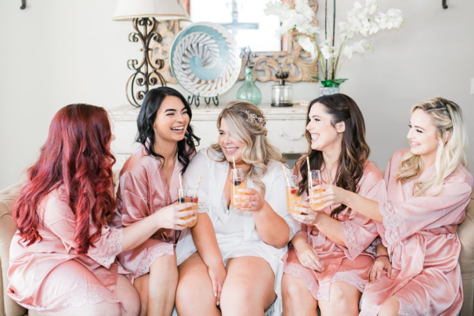 a bride and her bridesmaids toast before an intimate estate wedding