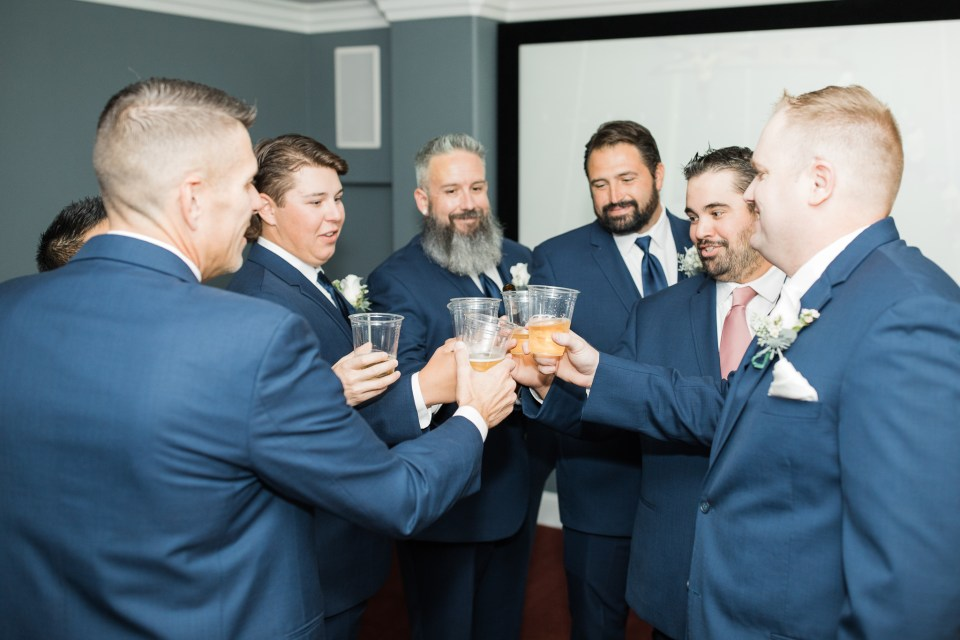 groom and groomsmen toast before an intimate estate wedding