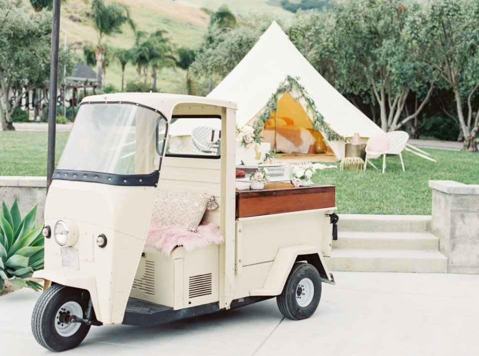 a vintage car used as a stand for cakes for planning a boho wedding