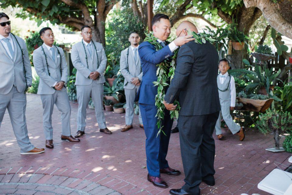 groom presents his father with a Hawaiian wedding lei