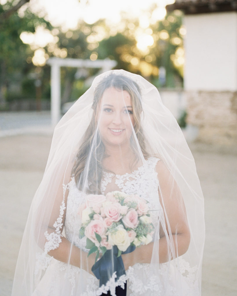 bride posing with veil and flowers