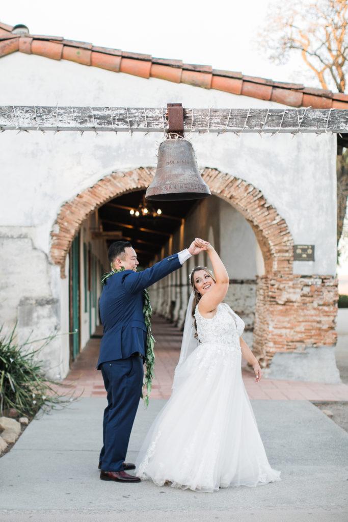 a groom twirls his bride before their wedding at Jardines de San Juan