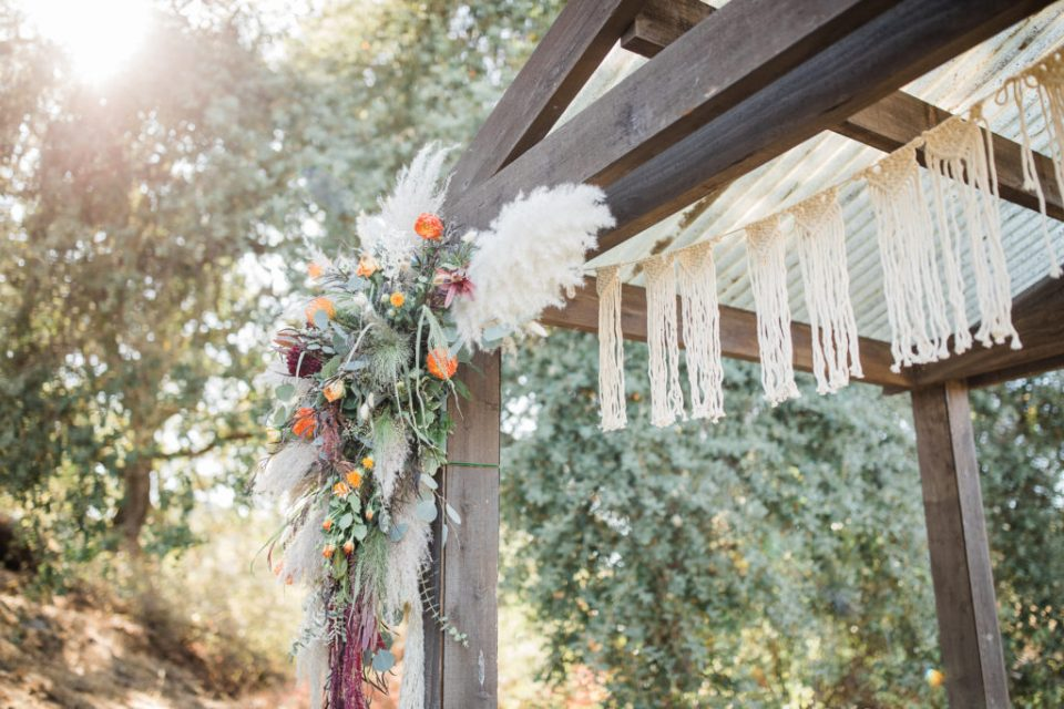 florals, greenery, and weavings decorating a wedding ceremony space by a hired wedding planner