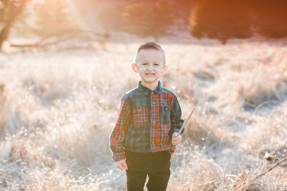a little boy smiles for the camera during family photos at Santa Teresa Park
