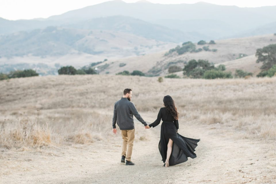 a couple walks through the fields during family photos at Santa Teresa Park