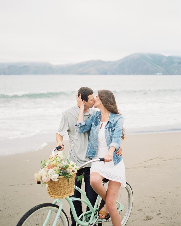 a couple kisses on a bike on the beach
