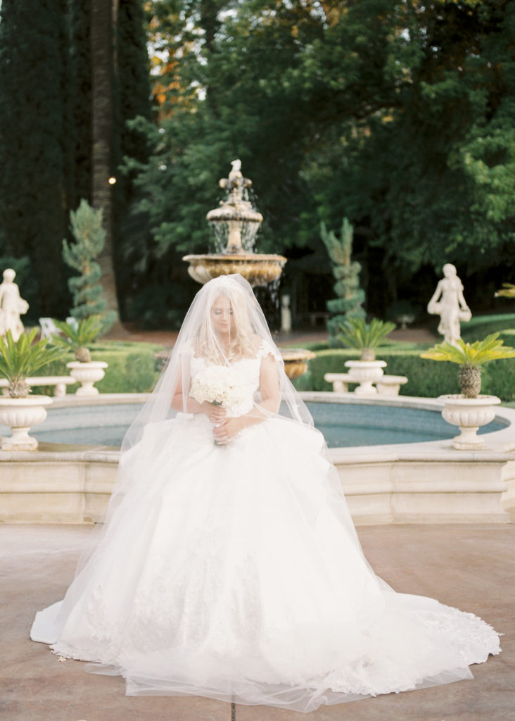 a bride poses for portraits in front of the fountain at her Grand Island Mansion wedding