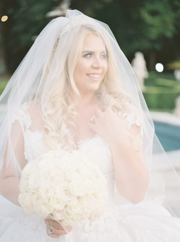 a bride covers her face with her veil at her Grand Island Mansion wedding