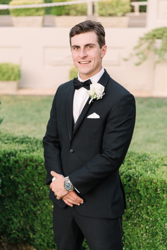 a groom poses for portraits at his Grand Island Mansion wedding