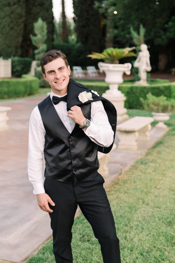 a groom tosses his jacket over his shoulder at his Grand Island Mansion wedding